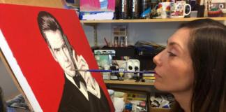 Ochrnutá umelkyňa maľuje štetcom za pomoci úst